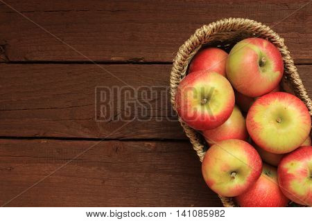 Apples in a basket on wooden background. Free space for text .