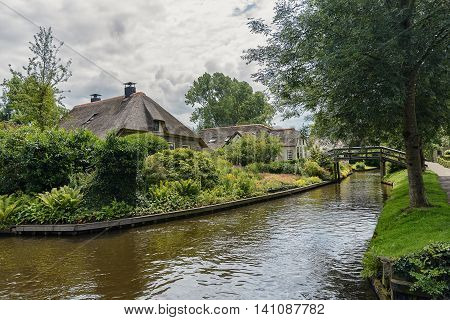 Cottage with a thatched roof and beautiful garden along a canal in Giethoorn, The Netherlands