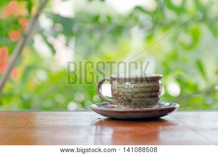 Hot Coffee Cup On The Wooden Table Near Garden