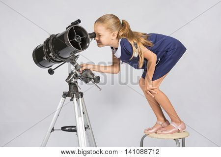 Seven-year Girl Standing On A Chair And Looks Ridiculous In The Eyepiece Of The Telescope Reflector