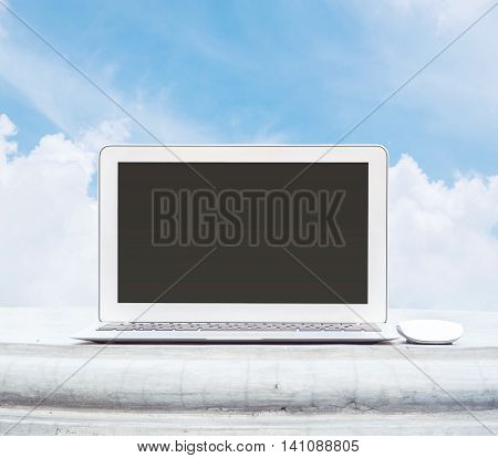 Closeup computer notebook with mouse on cement desk in the park with beautiful blue sky space background in work concept at the outdoor