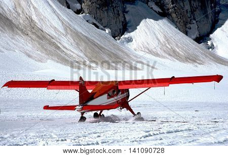 A plane rolling forward waking off from a Glacier in Alaska