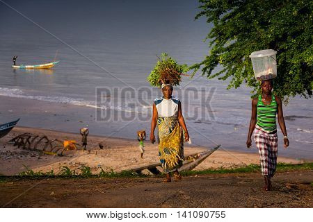 Yongoro Sierra Leone - June 02 2013: West Africa the beaches of Yongoro in front of Freetown woman carries vegetables to the market