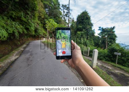 California, United States - July 23, 2016: Hand holding a cellphone to play Pokemon Go with walking path background