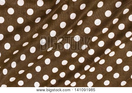 Closeup surface fabric pattern at old and wrinkled dark brown fabric handkerchief with white circle dot texture background