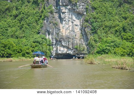 Tourists asia traveling in boat along nature the river and mountain. at Tam Coc portion Ninh Binh Province Vietnam. Rower using her feet to propel oars. landscape river and mountain