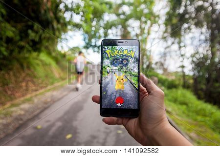 California, United States - July 16, 2016: Hand holding a cellphone to play Pokemon Go with blur background