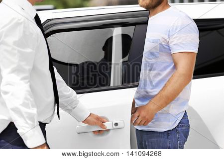 Man looking with salesman new car outdoors