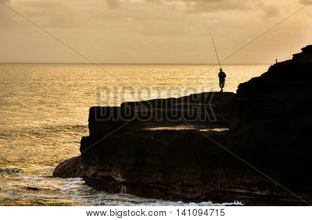 Silhouettes of fisherman with traditional fishing rod at Tanah Lot,Bali,Indonesia during sunset.