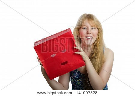 Young blonde girl has just removed red paper bag from head and laughs. Cheerful long-haired girl embodies openness and honesty. Upper body shot on white background