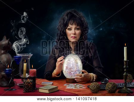 Stunning middle aged crystal gazer sitting at the desk surrounded by burning candles. Black haired female fortuneteller is scrying with big crystal egg and looks intently at the camera
