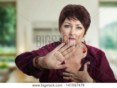 Middle-aged woman in maroon blouse asks dont take her picture. Woman in dark brown wig shows rejected gesture by right palm and looks at the camera irritatingly. Horizontal indoors upper body shot