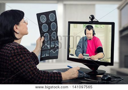 Virtual doctor attentively looks at mans brain x-ray results. Physician sits opposite monitor at the black desk. At the same time, man in headset checks his blood pressure