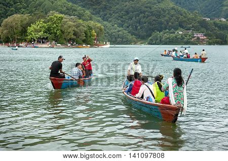 Pokhara Nepal - July 25, 2011 : Tourists enjoy boat ride in vast Phewa Lake, natural colors. Phewa lake is a tourist spot located at an altitude of 742 m