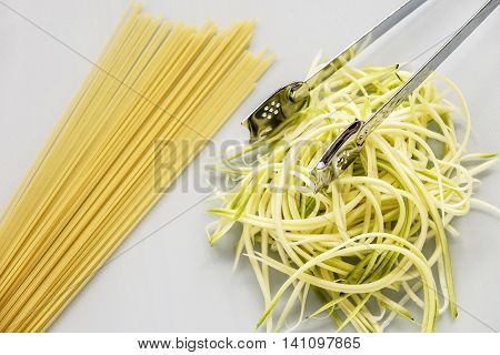 Spiralized zucchini or courgette as an alternative to spaghetti with stainless steel kitchen serving tongs on white chopping board