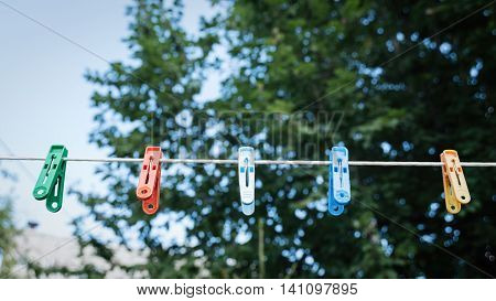 plastic clothespins, laundry hook, colorful, pegs, rope, outside, sun, greensummer decorationspegspinvillageblueskyplastic pegsyellow clothes pinsred clothespinsblue clothespinsropeorange pegs