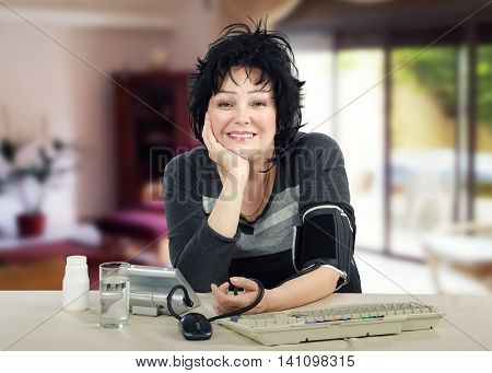 Cheerful mature woman measures her blood pressure. Smiling black haired woman sits at white desk and looks at the camera.  She likes looking after for her health