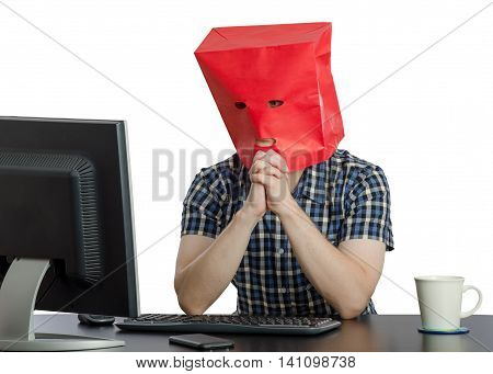Introverted guy in red paper bag asks online psychologist how to overcome shyness. The young man looks to monitor sitting at black desk
