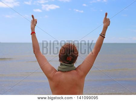 young girl with thumb up on the seashore in the summer