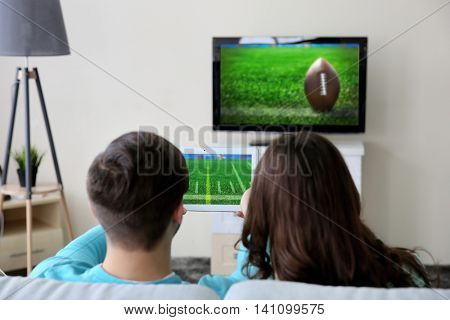 Young couple watching football game on tv at home.