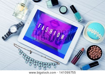 Digital tablet with woman's accessories on white wooden table background, top view. Fashion blog concept