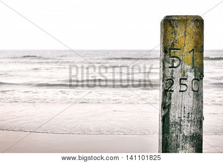 Wooden pole or pillar on the beach. Copy space and focus on the foreground.