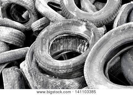 Stack of old car tires or wheels. Full frame shot of old, weathered tires. Monochrome toned image.