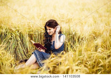 Portrait of cute pretty happy young woman in dress reading book sitting on a grass in field straightens hair. Sunny morning.