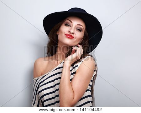 Fun Grimacing Young Woman In Hat With Red Lipstick On Blue Background