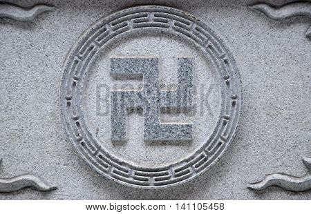 The chinese character wan symbolizing resignation in Buddhism carved in stone within the Jile temple (temple of bliss) in Harbin China in Heilongjiang province.