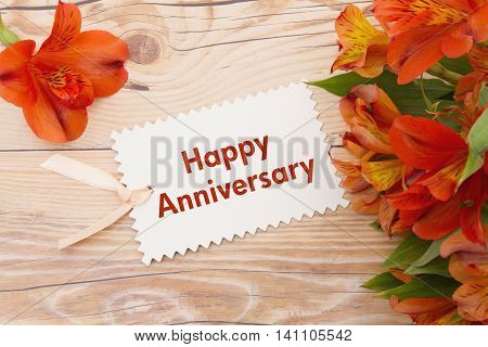Happy Anniversary Greeting Some lilies on weathered wood with Happy Anniversary Gift Card and copy space for your message