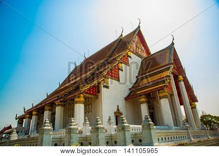 Religious Building With A Triangular Roof On Blue Sky Background. Ayutthaya Thailand.