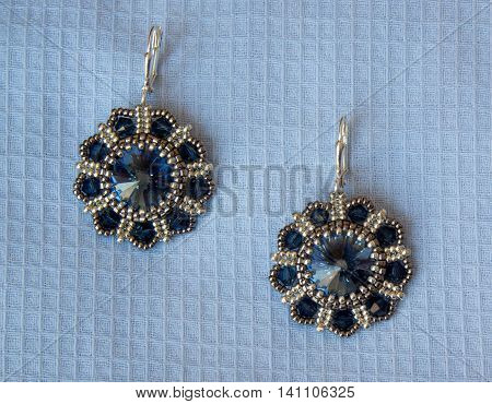 Earrings with blue stones on the light background