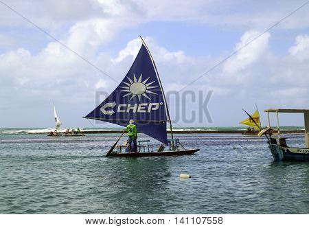 Pernambuco Brazil July 6 2016: An unidentified fisherman in Chicken Beach with typical sail boats in Ipojuca City near barrier reef northeast Brazil