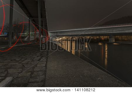 Night shot of a bridge in Regensburg, Bavaria, Germany with the illuminated europakanal and mainstreet