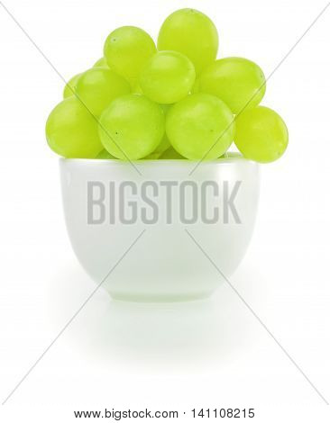 Green grapes in bowl on white background.