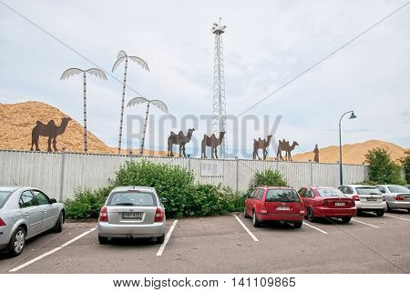 KOTKA, FINLAND - JUNE 26, 2016: Oasis. Composition with camels on the fence of the wooden chips storage by company of Kotkamills Oy