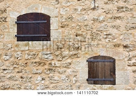 Two old classic style windows on rude facade.