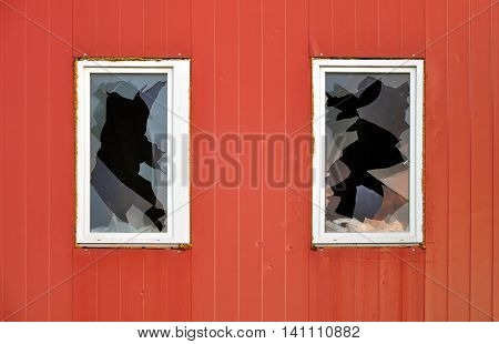Abandoned industrial building. Red wall of sandwich-panels and two windows with broken glass
