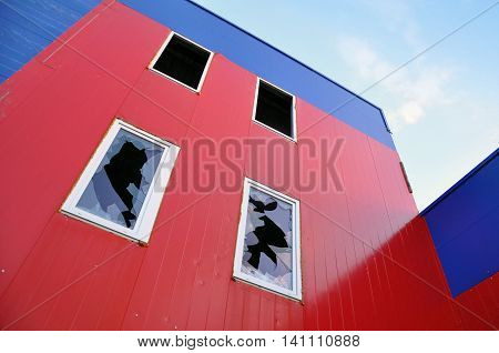 Abandoned industrial building. Looking up at the red and blue wall of sandwich-panels and windows with broken glass