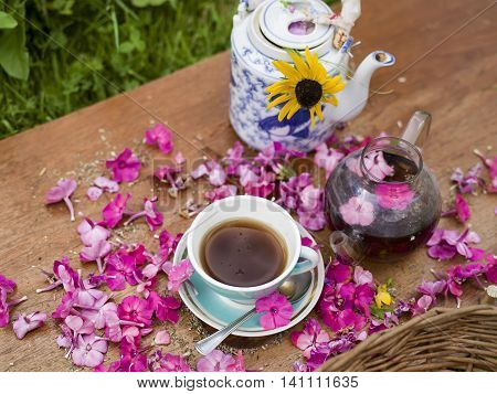 Herbal tea in tea pots and tea cups the phlox are spread out on the table a garden in the blurred background