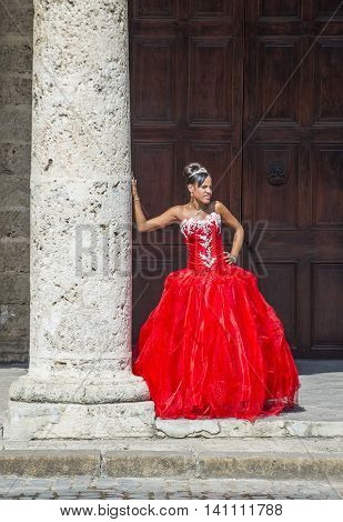 HAVANA CUBA - JULY 18 : Cuban woman with red dress in old Havana street on July 18 2016. The historic center of Havana is UNESCO World Heritage Site since 1982.