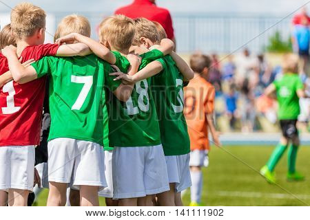 Kids on soccer field. Youth football team united shout team before the final game. Team work sports background