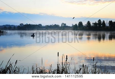 A fisherman in a boat floating on the water in the dawn sun in the fog