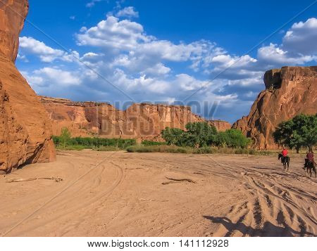 Apache County reserve, Arizona, United States - June 16, 2007: Navajo Indian in red shirt on a black horse, rides on the sand of the valley of Canyon de Chelly National Monument