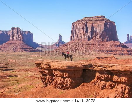 Monument Valley, Arizona, United States- June 17, 2007: Navajo Indian on a black horse at John Ford Overlook, in scenic landscape of Monument Valley Tribal Park