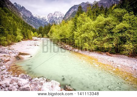 Beautiful landscape view with river and snowed up mountains in Triglav national park in Slovenia. Traveling slovenian Alps