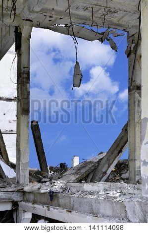 Blue sky in the opening wall of the destroyed building and concrete debris.