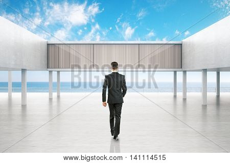 Businessman walking towards concrete exterior by the sea on bright blue sky background. 3D Rendering