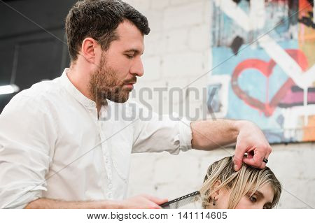 Male hairdresser making a haircut for a client in professional hairdressing salon.